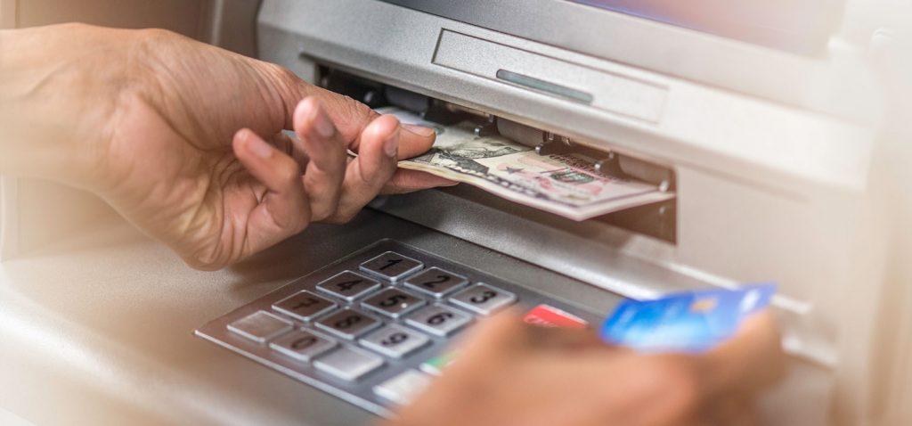 hand feeding a bill into an ATM